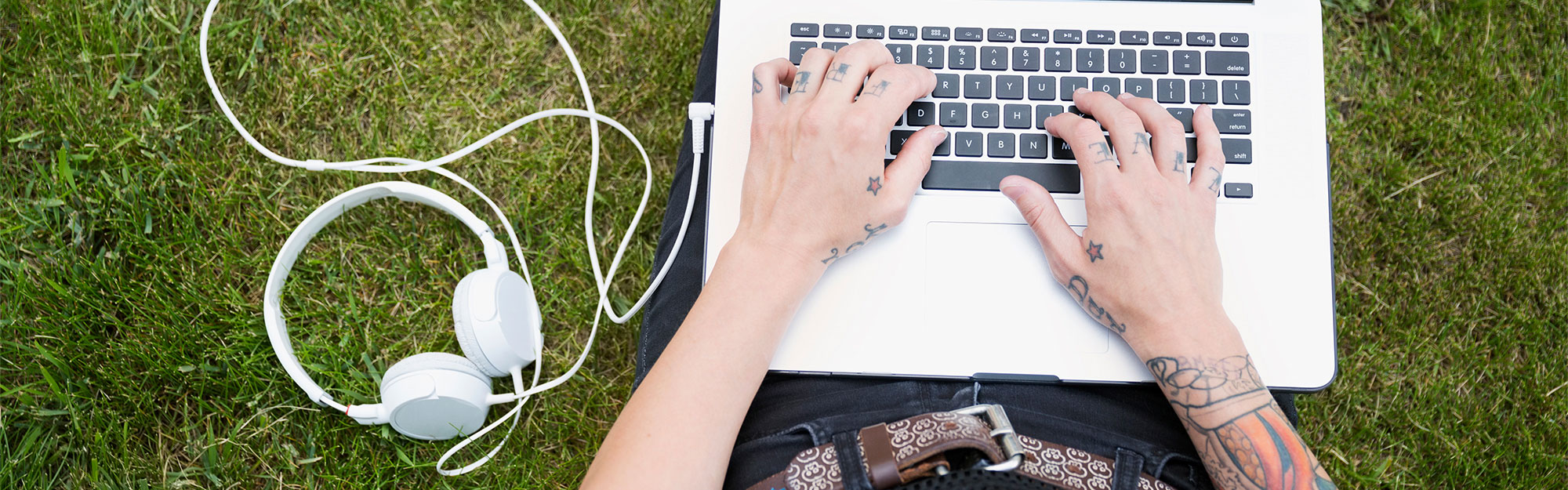 Young woman with tattoos using laptop in the grass.
